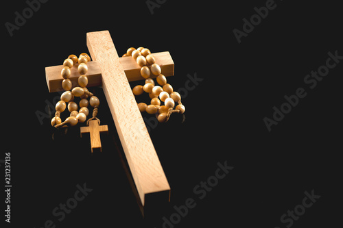 Fototapeta Wooden illuminated crucifix with a rosary on a black background