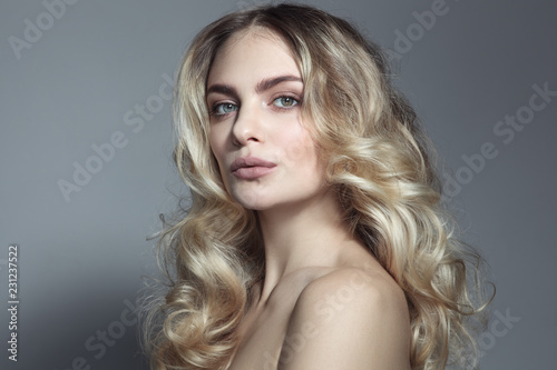 Young beautiful blonde woman with long curly hair Fototapet
