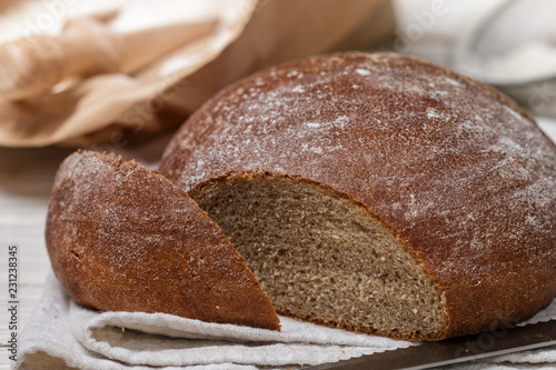 Freshly baked homemade bread, flour and a knife on an old wooden table. Rustic style. Selective focus