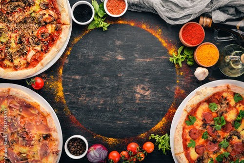 Foto auf AluDibond Pizzeria A set of Italian pizza. Italian cuisine. On a black wooden background. Free copy space. Top view.