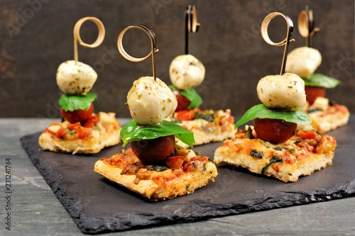 Spoed Fotobehang Voorgerecht Caprese pizza skewers with mozzarella, basil, and tomatoes. Appetizers against a dark stone background.