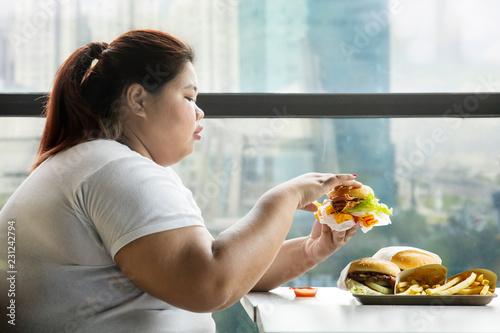 Fotomural  Overweight woman eats hamburger in a restaurant