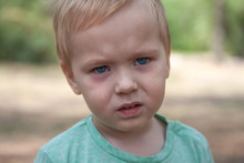 Close Up Portrait Of Cute Caucasian Baby Boy With Serious Expression In Blue Eyes. Moment Of Tears. Blonde Hair. Outdoors, Copy Space.