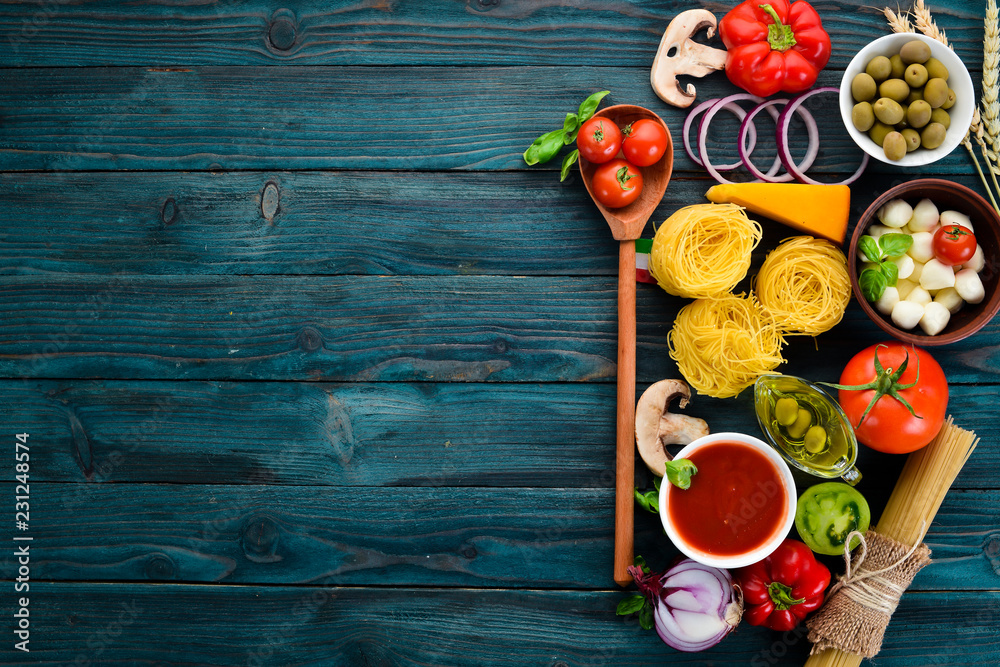 Fototapety, obrazy: Ingredients for cooking pasta. Dry pasta. Mushrooms, sausages, tomatoes, vegetables. Top view. On a blue wooden background. Free copy space.