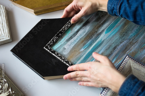Picture framing. Choosing decorative frame for a painting. Woman's hands and samples of frames.