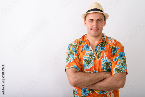 Fotografering  Studio shot of young muscular tourist man wearing hat with arms