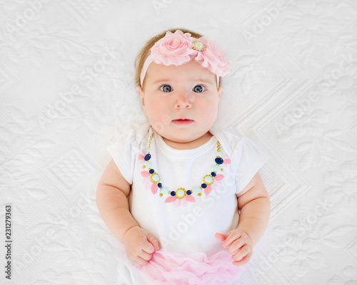 curious baby girl 4 months old wearing tutu and headband