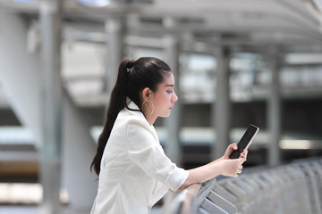 Fototapeta Pretty young Asian woman using mobile smart phone on street of city background. Social network concept