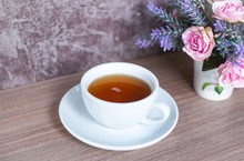 A Cup Of Chinese Tea On Wooden Table. Beverage For Healthy With Rose Flower In Pot
