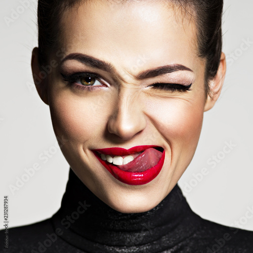 Fototapeta Young woman with bright face expression. Girl winks one eye obraz