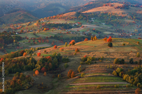 Fotobehang Landschap Fall in Slovakia. Meadows and fields landscape near Hrinova. Autumn colored cherry trees at sunset
