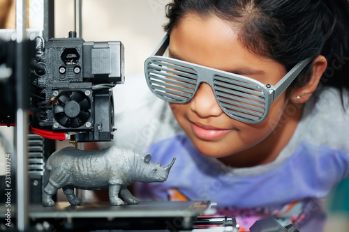 Obraz Cute girl with cool 3d printed shutter shades is watching her 3d printer as it prints her 3d model of a rhinoceros. - fototapety do salonu