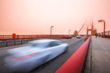 Cars Crossing The San Francisco, Californian Golden Gate Bridge From The Presidio Pacific Point To The North At Sunset Light. People Along The Bridge In The Fog. Motion Blur Effect.