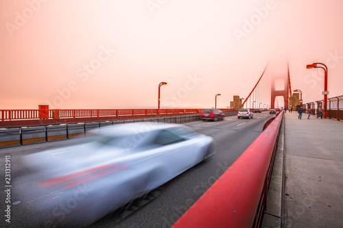 Staande foto Amerikaanse Plekken Cars crossing the San Francisco, Californian Golden Gate Bridge from the Presidio Pacific point to the north at sunset light. People along the bridge in the fog. Motion blur effect.