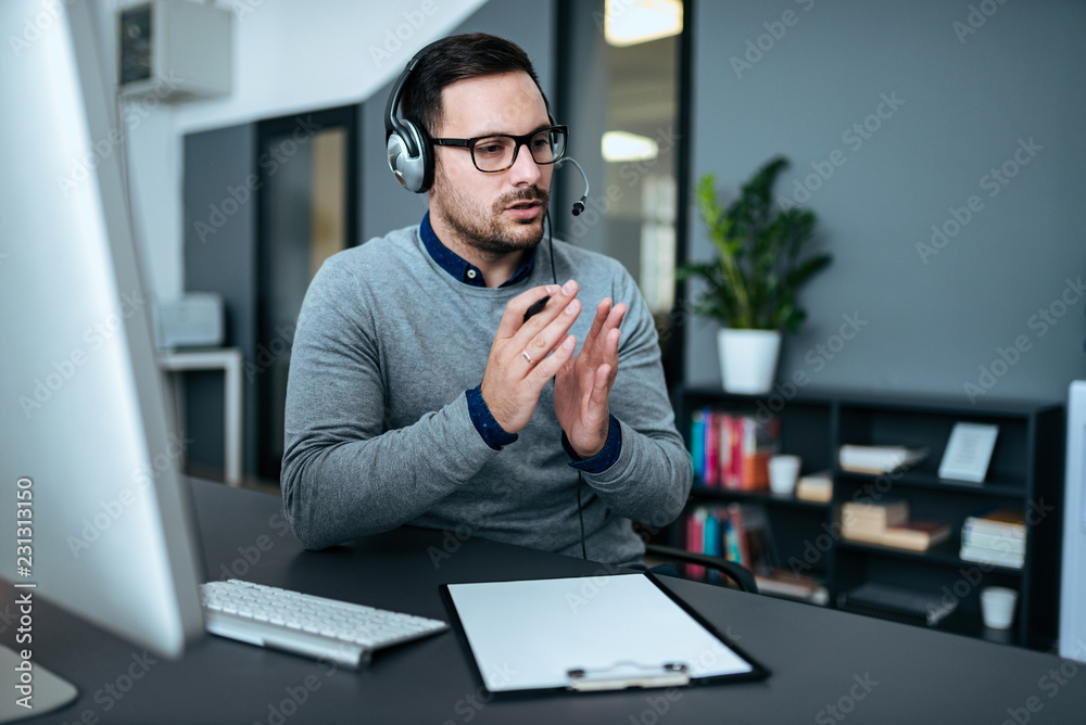 Fototapeta Young handsome male customer support phone operator with headset working in his office.