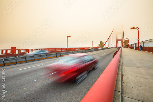 Poster Amerikaanse Plekken Red car crossing Golden Gate Bridge from Presidio Pacific point to the north. Motion blur effect. San Francisco, California, United States. Typical fog in summertime. Perspective view.