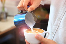 Barista Using Pitcher For Pouring Milk To Cup Of Coffee Latte Tulip Pattern On Top
