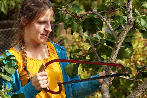 Fotografie, Obraz  junge Frau beschneiden mit einer Säge einen Baum