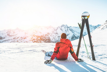 Skier athlete sitting in alpes mountains on sunny day - Adult man enjoying the sunset with skies gear next to him - Winter sport and vacation concept