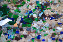 Broken Glass Bottles On White Sand. Bottles Is Green And Blue Colour. Trash On The Sand. Ecological Problem.