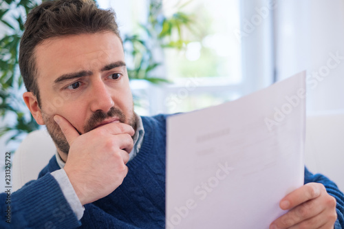 Fotomural  Worried man reading bad news document at home