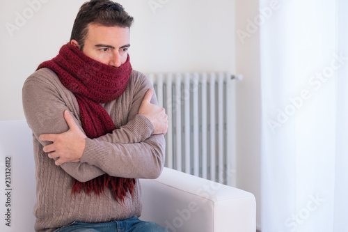 Man feeling very cold at home with warm clothes Fototapet
