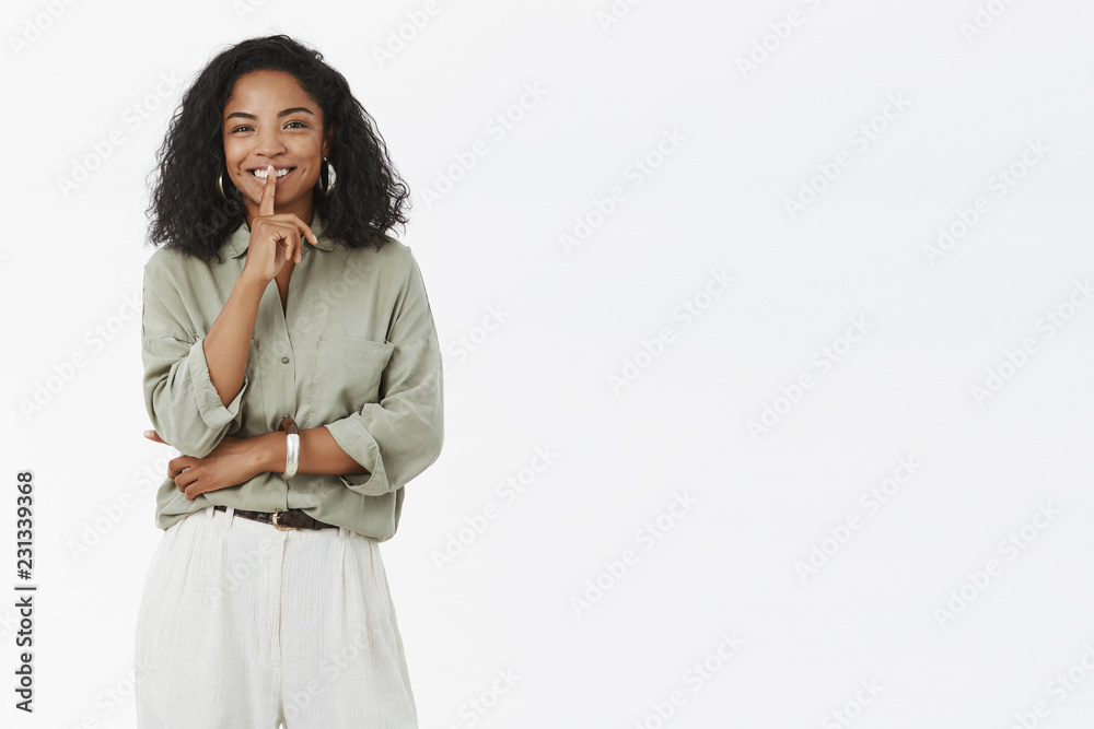 Fototapeta Shh I prepare surprise. Joyful charismatic and stylish african american girlfriend with curly hairstyle shushing at camera and smiling with joyful look telling secret against gray background