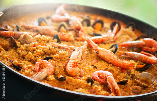 Paella. Traditional spanish food, seafood paella in the fry pan with mussels, king prawns, langoustine and squids. Cooking paella outside