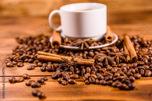 Foto op Canvas Cafe Cup of hot coffee, star anise, cinnamon sticks and scattered coffee beans on wooden table