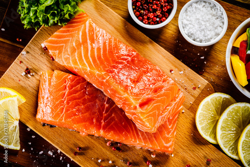 Fresh raw salmon fish served on cutting board on wooden table