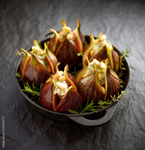 Papiers peints Buffet, Bar Fresh figs stuffed with gorgonzola cheese, pine nuts and herbs in a black dish on a dark, stone background. Excellent, tasty, vegetarian appetizer