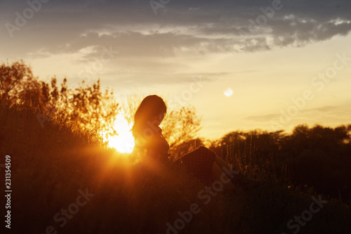 Foto auf AluDibond Braun silhouette of a young woman sitting on a hill at sunset, a girl walking in the autumn in the field