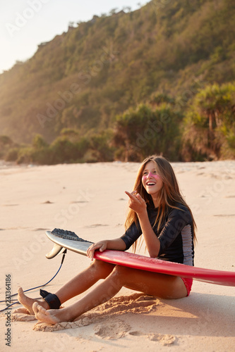 Photo of glad European female surfer in wetsuit, points with index finger in distance, observes tricks of her companion on water, holds surfboard, sits at sandy beach near cliff. Lifestyle concept