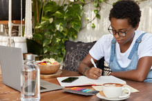 Serious Dark Skinned Female College Student Makes Research, Watches Webinar For Education On Laptop, Makes Notes In Diary For Better Memorizing, Surrounded With Mobile Phone And Aromatic Cappuccino