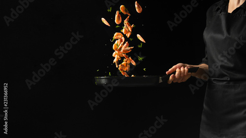 Professional chef prepares shrimps with greens. Cooking seafood, healthy vegetarian food, and food on a dark background. Horizontal view.