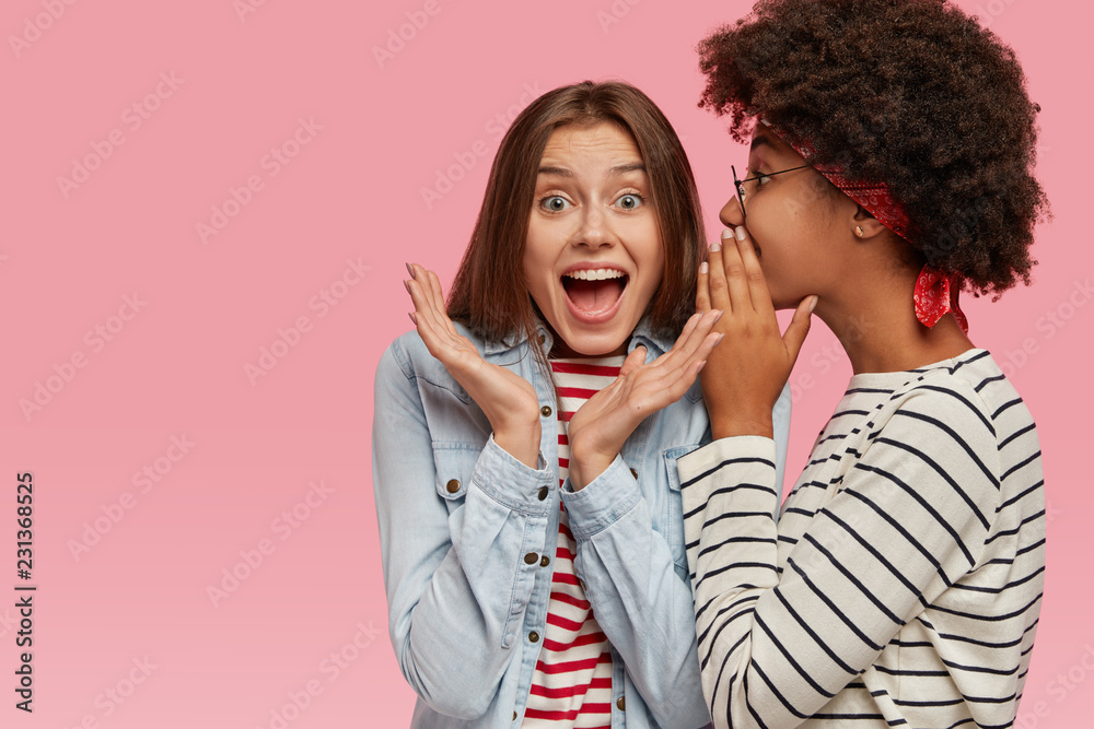 Fototapety, obrazy: Emotional European woman clasps hands and exclaims loudly as hears rumors from best friend. Afro American woman whispers secret at companions ear, stands sideways, gossip together, stand indoor