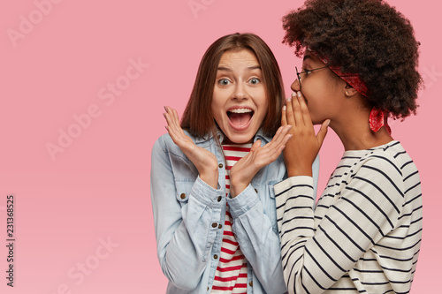 Photo  Emotional European woman clasps hands and exclaims loudly as hears rumors from best friend