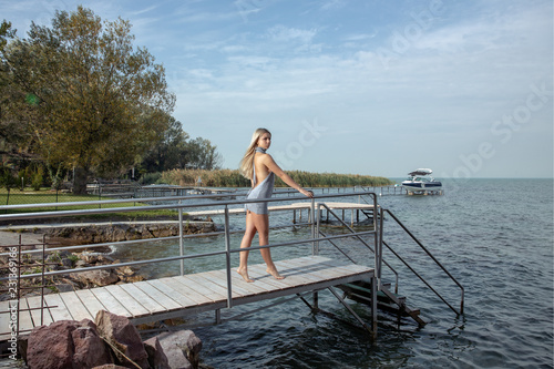 Photo  Woman on the pier in silver swimwear at Balaton lake