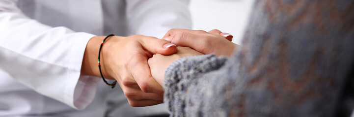 Friendly female doctor hold patient hand in office during recept