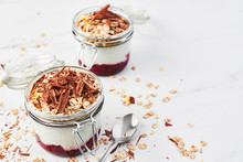 Healthy Breakfast. Two Jars Of Healthy Yogurt With Strawberry Sauce, Oat And Chocolate On White Marble Table. Close Up With Copy Space.