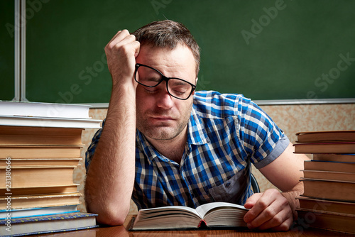Fotografie, Obraz  A tired and tortured disheveled student in glasses is sleeping at a table with stacks of books against the background of a cool blackboard