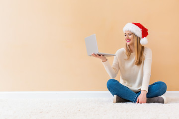 Fototapeta Young woman with santa hat using her laptop on a white carpet