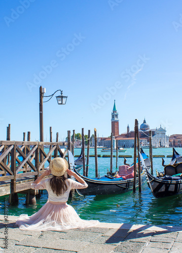 Foto op Aluminium Gondolas girl on berth with gondolas in Venice