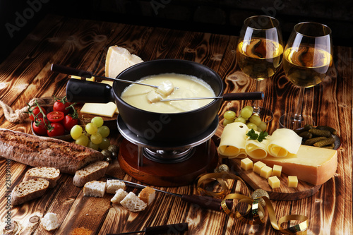 Valokuva  Gourmet Swiss fondue dinner on a winter evening with assorted cheese