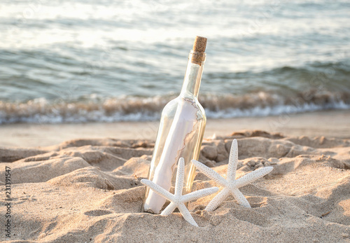 pair of tropical white starfish in beach sand with paper message in a bottle