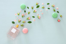 Top View Image Of Perfume Bottle With Rose Petals Flowers And Macaroon Over Pastel Blue Background.