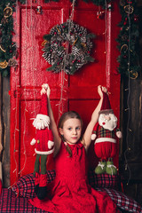 A girl in a red dress holds toy Santa and an elf in her hands.