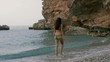Young attractive woman walking on wild rocky beach. Slim sporty girl in bikini resting outdoors. Exclusive slow motion 4k footage. Back view.