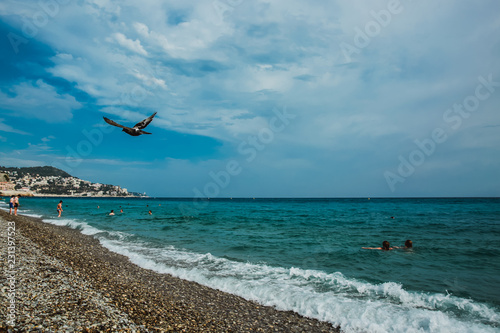 Spoed Foto op Canvas Nice People enjoying sunny weather on the beach of Mediterranean sea Nice, France, Europe.