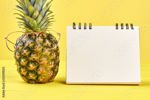 Pineapple in glasses and blank notepad. Fresh exotic pineapple wearing golden eyeglasses and empty notebook on colorful background, front view.